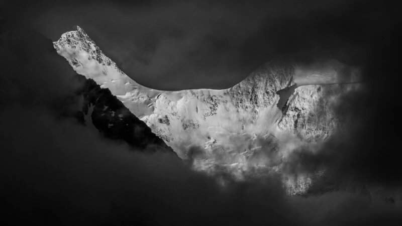Black and white photo of Belukha's white snow covered mountain face surrounded by dark and ominous clouds.