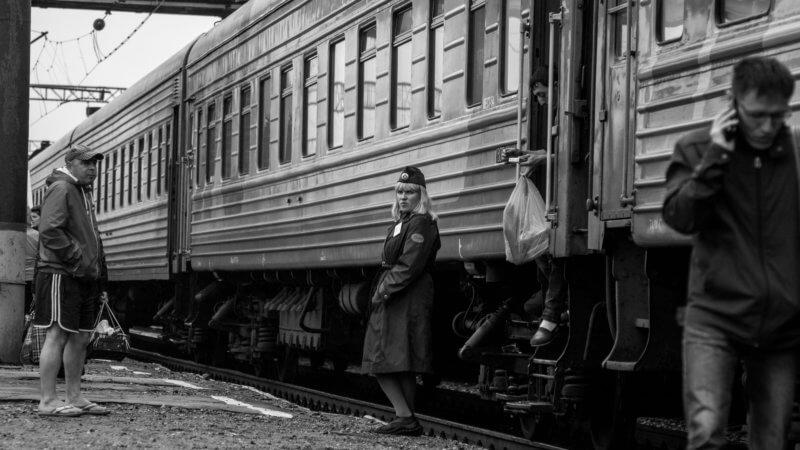 Black and white photo of a serious looking train conductor stood beside her train carriage.
