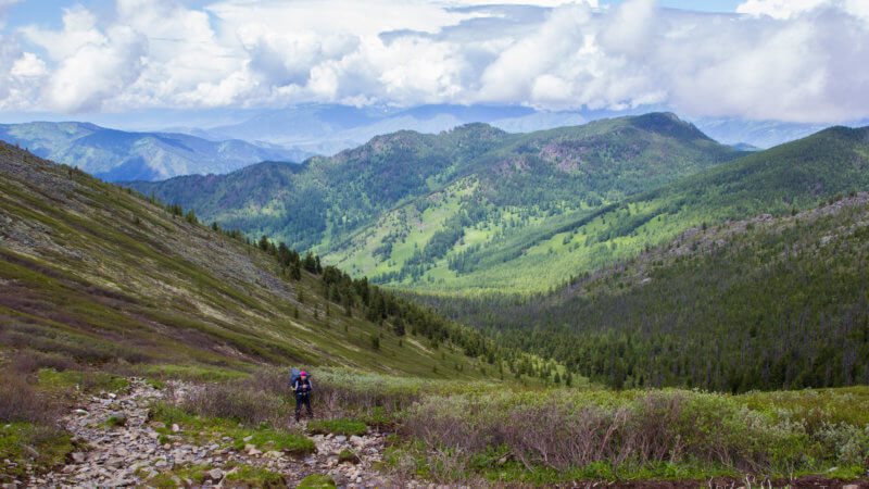 Wide view of a hiker ascending a hill out of a remote alpine valley.