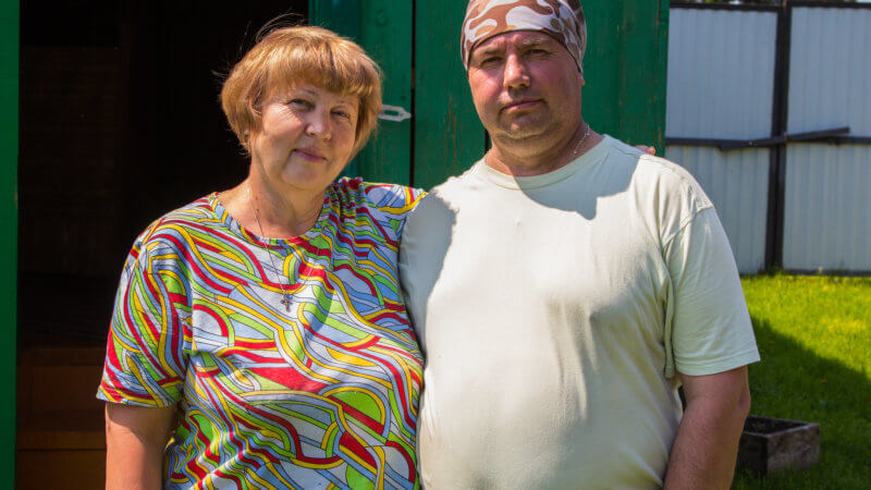 A man and woman, one with a colorful shirt and another with a bandana, posing for a photo.