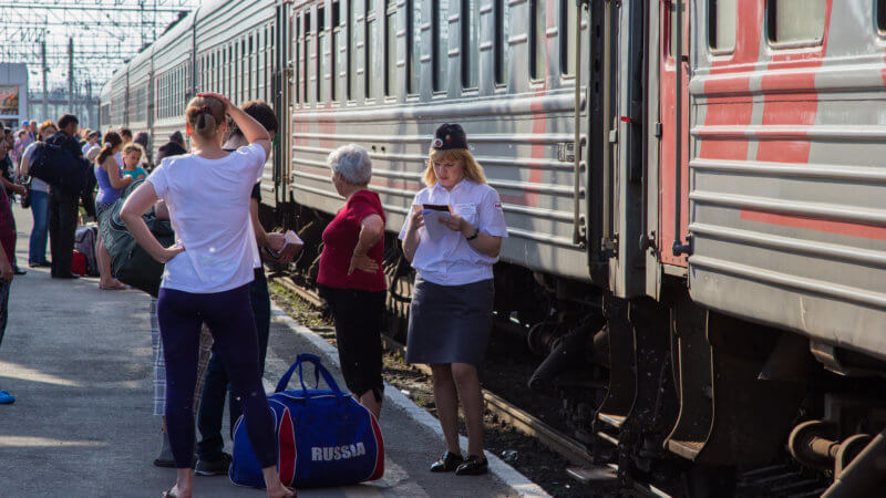 A train conductor stood next to a train carriage and passengers, looking at her paperwork.
