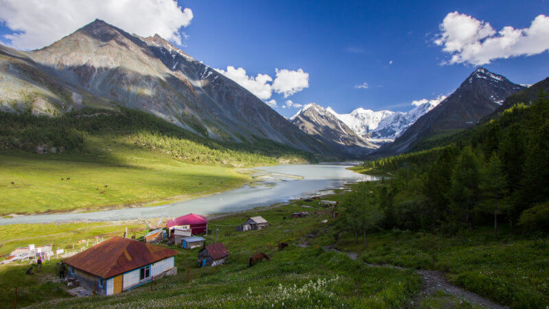 A wide angle view of a few houses next to a big lake and mountain valley near Belukha.