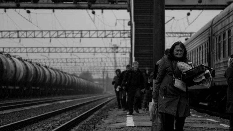 Black and white photo of an old woman at a train station in Russia looking tired and laden with bags.