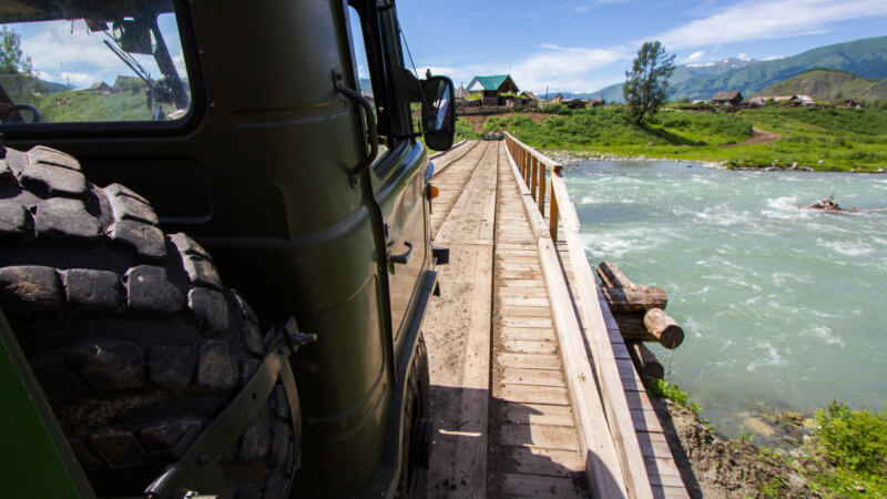 Side-view of green truck crossing over a wooden bridge.