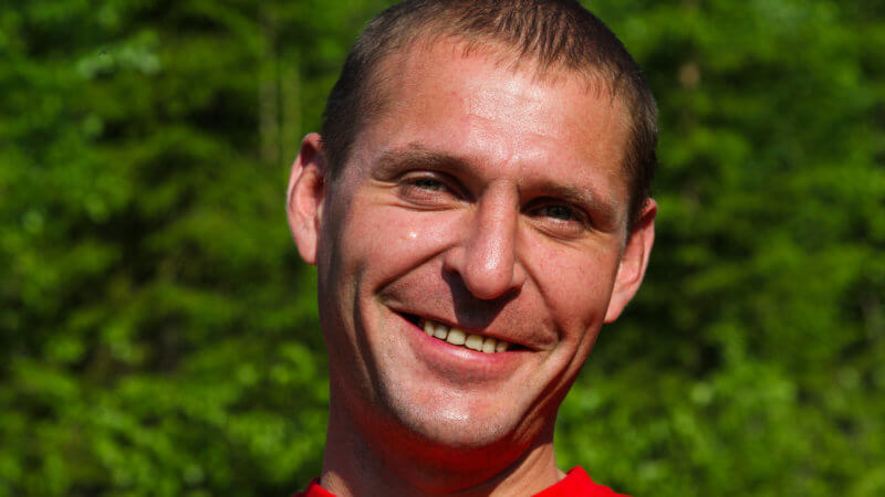A Russian man smiling with short hair and a red t-shirt.