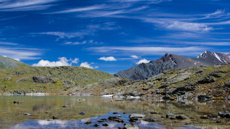 A crystal clear alpine lake, blue skies, white clouds and rocky ridges in the distance.
