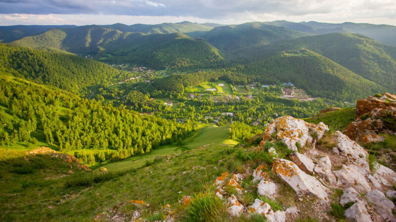 Looking down from atop a mountain into a small village nestled in a wooded valley.