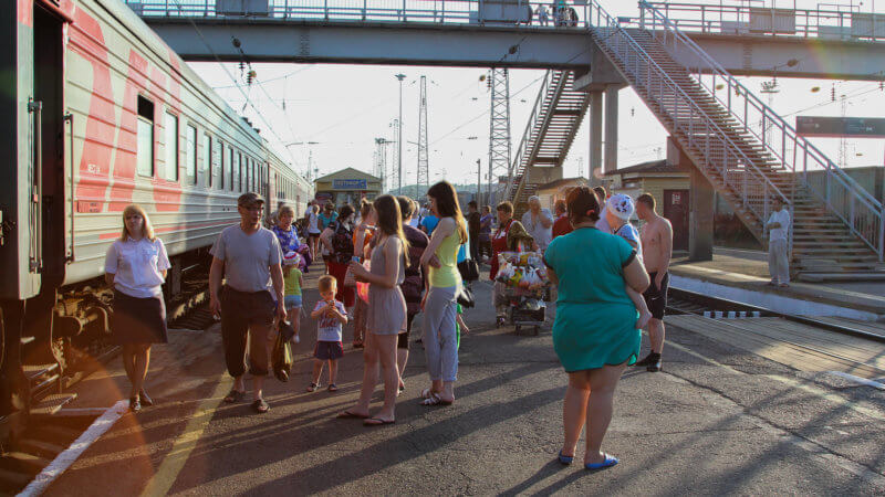Large groups of passengers stretch their legs on a train platform somewhere in Siberia.