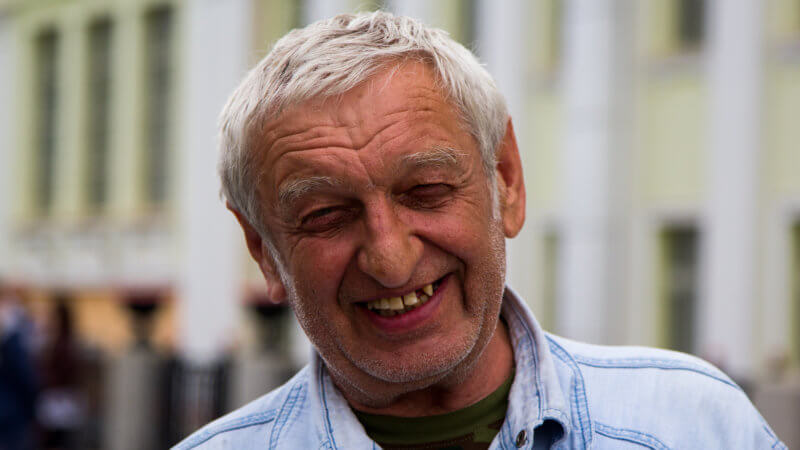 Portrait of an older Trans-Siberian train passenger with grey hair and cheeky smile.