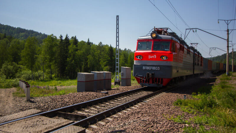 A red cross country cargo train travelling through the Altai Mountains.