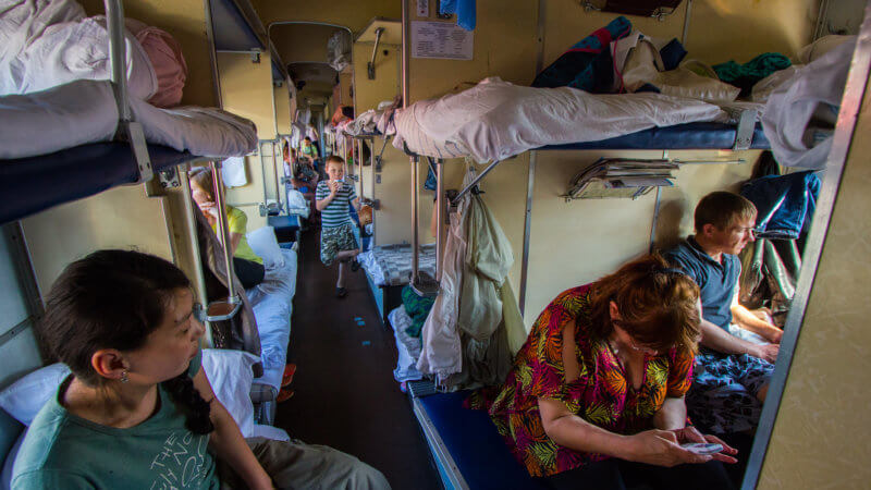 Two Russians and one Mongolian sit on a bunk beds on the Trans-Siberian Express train.