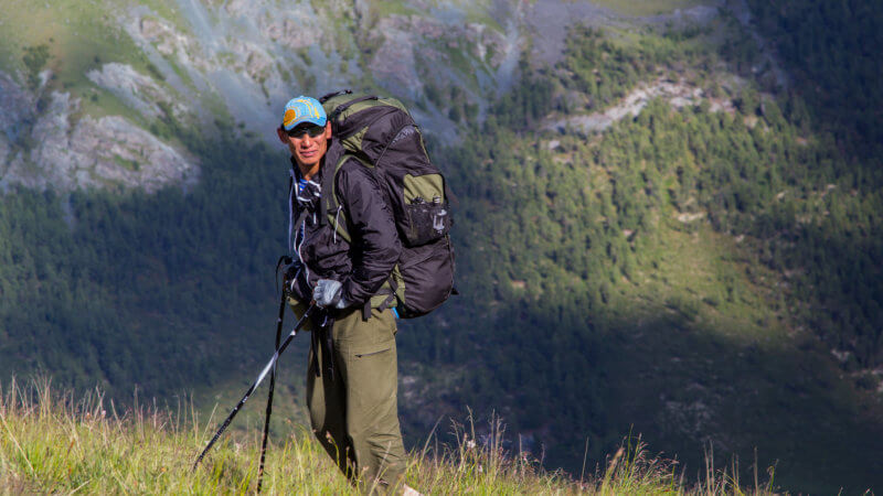 A hiker from Kazakhstan poses with hiking poles and a big backpack.