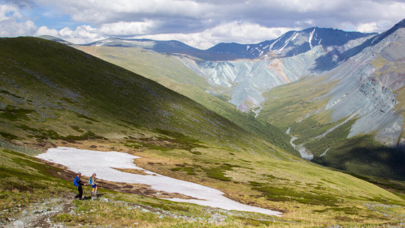 Two hikers descending down a big hill and into a deep valley.