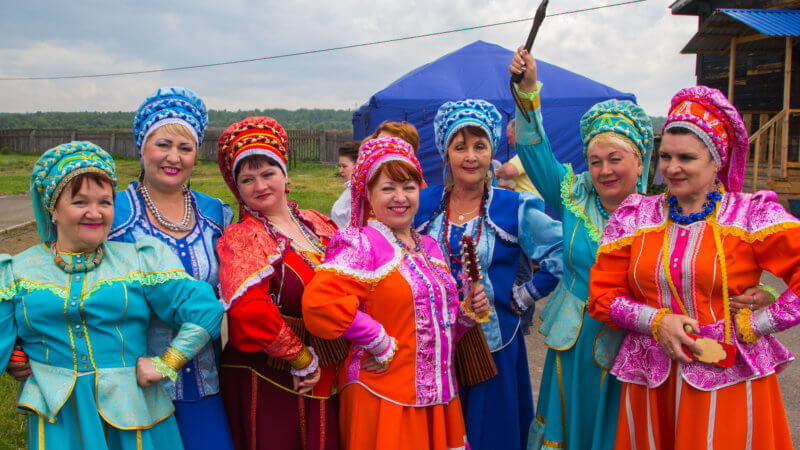 Russian woman in Yeniseysk wearing brightly-coloured traditional clothing and one swinging a whip.