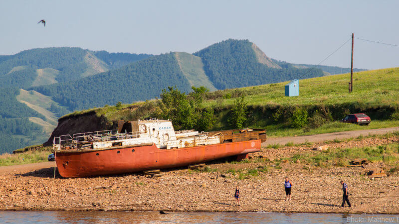 Three boys in the distance play next to an abandoned red hulled fishing vessel that's aground.