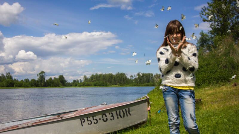 A girl with white and black polka dot sweater releases butterflies from her hands.