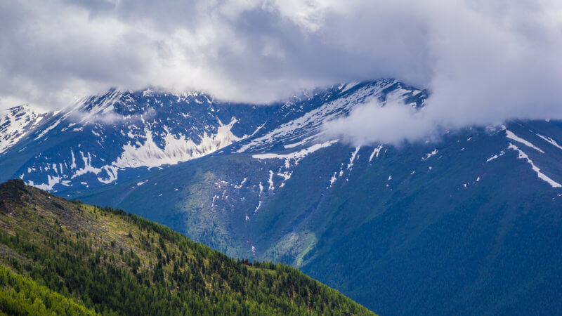 An forest covered hillside overlooks higher snow-covered mountains enshrouded in cloud.