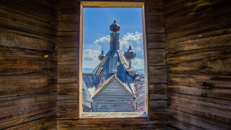 The top of a Russian Orthodox church framed through an old wooden window frame.