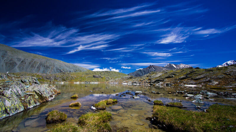 Wide angle view of a crystal clear alpine lake with white, wispy cirrus clouds in the sky.