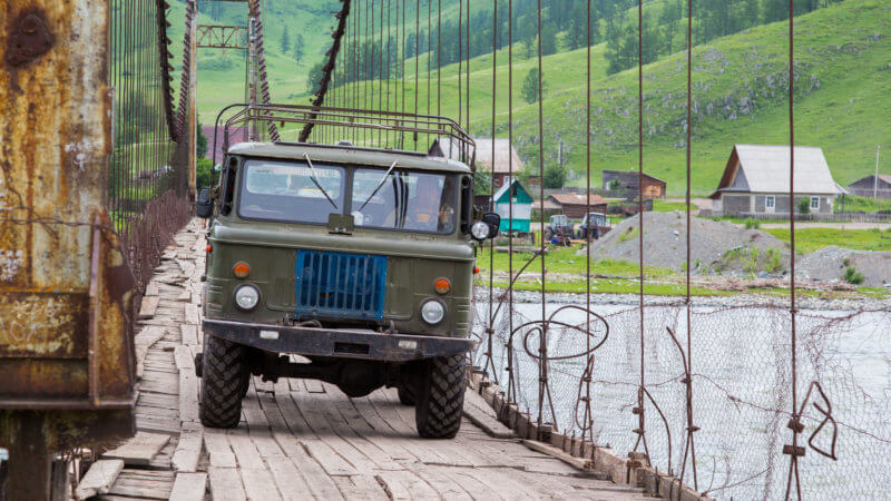 A green Soviet-era truck crossing an old suspension bridge formed out of wooden planks.