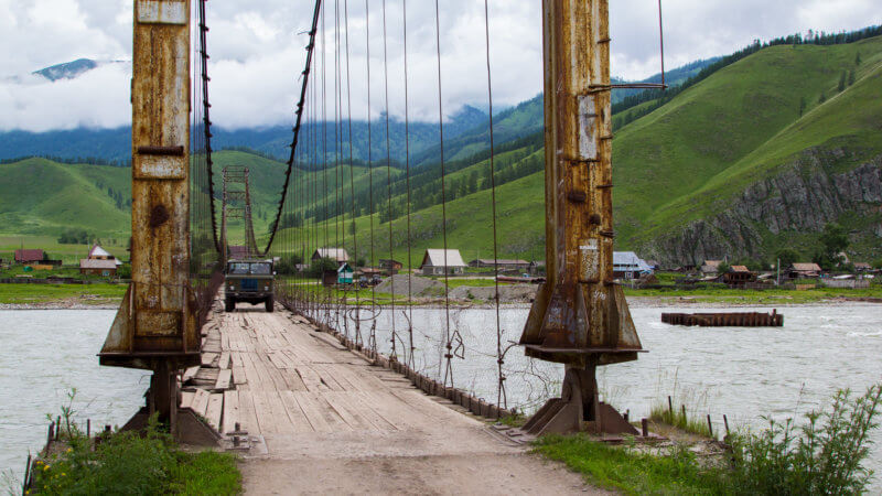 An Soviet-era truck drives over a rusty bridge suspended over the Biya Rivers in the Altai Republic.