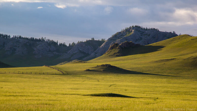 Green pastures and shadows cast by small hills with rocky mountains in the background.