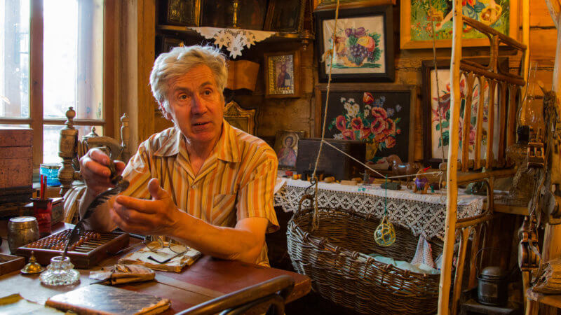 A historian in Yenisei sits in a museum, explaining the artefact he's holding.
