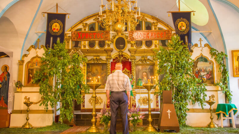 An old man stands in front of an ornate orthodox Christian shrine.