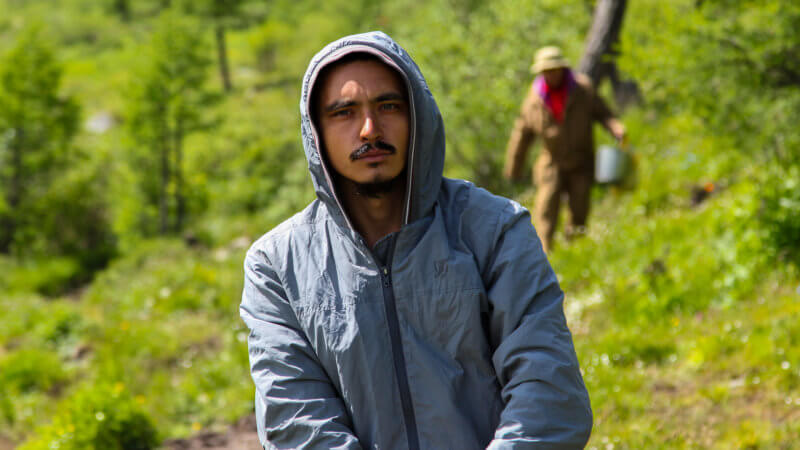 A Russian hiker with moustache poses for camera wearing a grey hoody top.