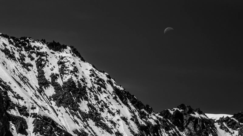 Black and white photo of a snow-covered mountain ridgeline with faint half moon in sky.