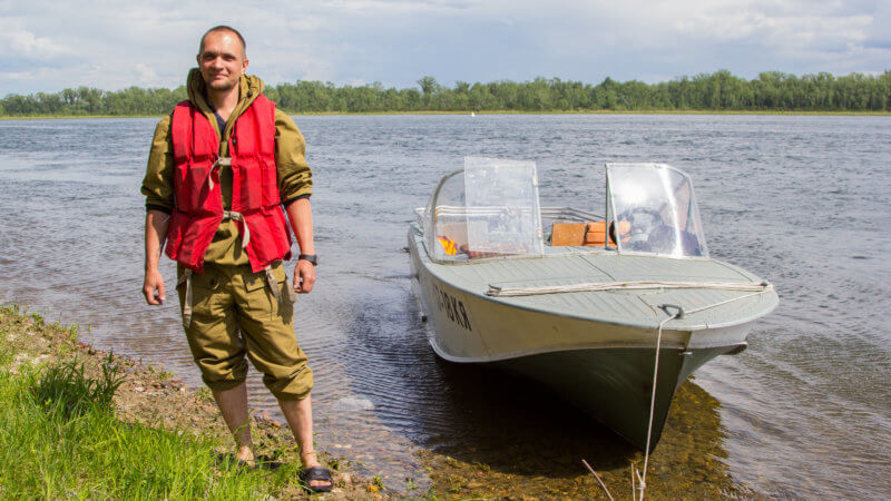 A speedboat driver stood beside his boat wearing a red lifejacket and green camouflage clothing.