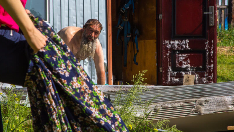 An orthodox Russian priest crouches over a pail of water to wash himself.