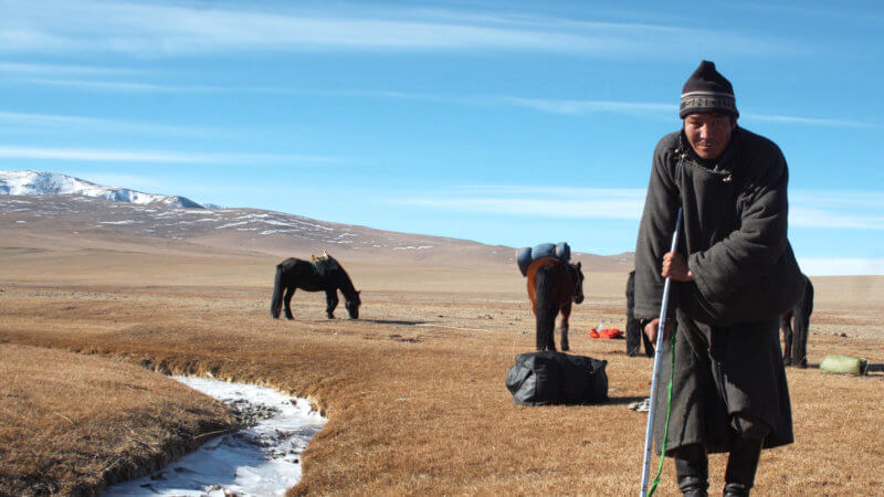 A crippled Mongolian man poses for a photo, propping himself up with his crutch.