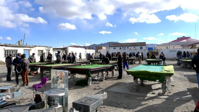 An open air snooker parlour in Olgii, western Mongolia, with dozens of men playing.