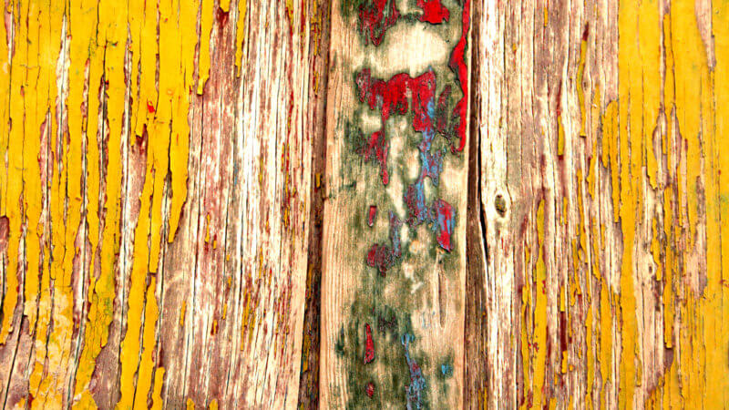 Very close up look at a wooden yurt door with multi-coloured paint flaking away from age.