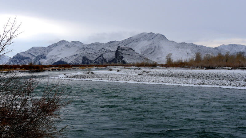 Khovd River with snow covered hills in the background.