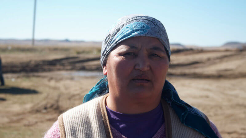 A serious-looking, but friendly, Kazakh woman looks into the camera.