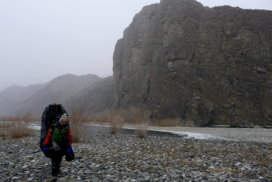 Jamie walking beside the Khovd River in winter with a packraft on his back.