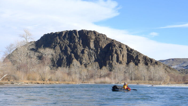 A packrafter descends a cold Khovd River with dry forest and rocky mountain in background.