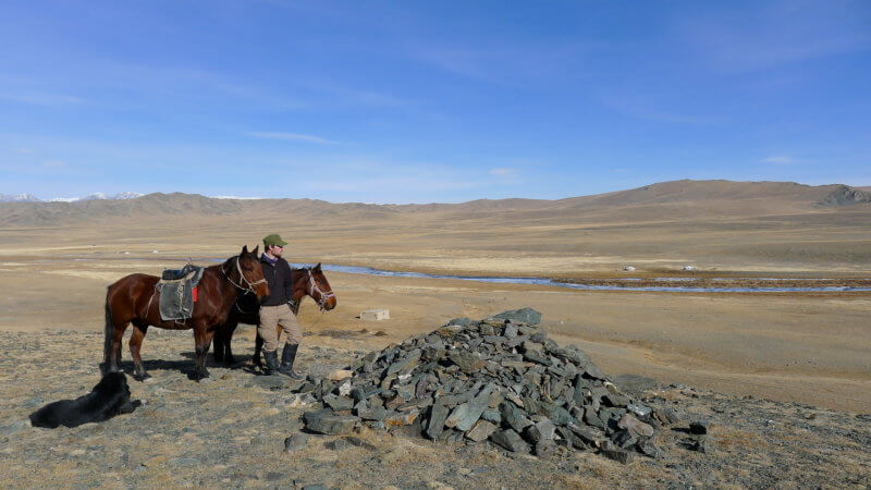 Jamie holding two horses atop a small Mongolian hill with a cairn.