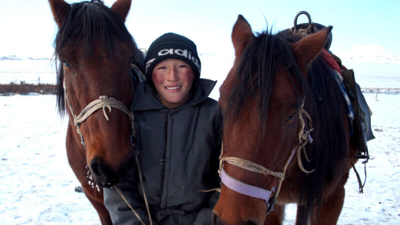 A Kazakh boy in winter grins while holding two horses either side of him.