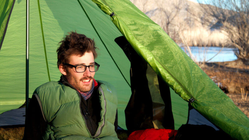 Jamie Maddison wearing a green gillet, sits in front of a green floorless tent in the morning.
