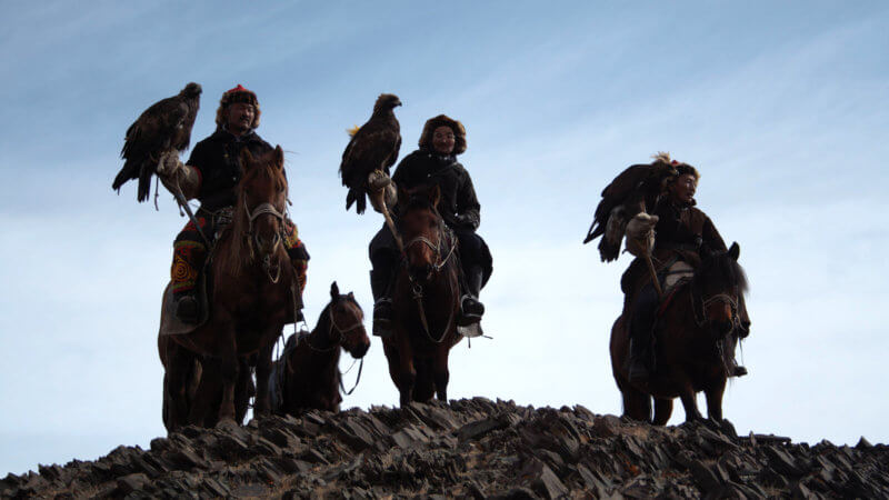 Three eagle hunters with eagles on arms look into the distance.