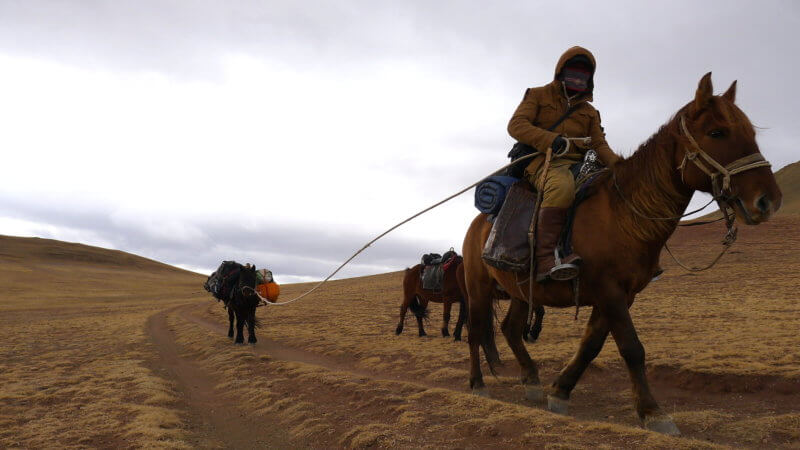 Kazakh horseman riding on horseback and towing a pack animal with a rope.