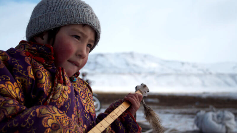 A Kazakh boy wearing a wool hat and traditional clothing holds a dombra musical instrument.