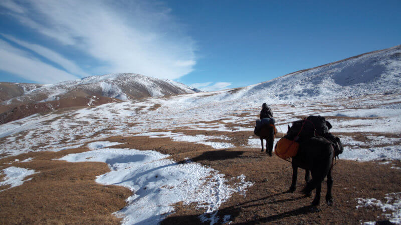 A Mongolian horseman pulls his packhorse up a mountain dusted in light snow.