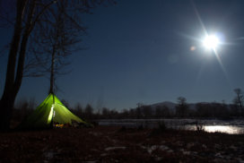 A night time shot of a green tent beside a frozen river in moonlight.