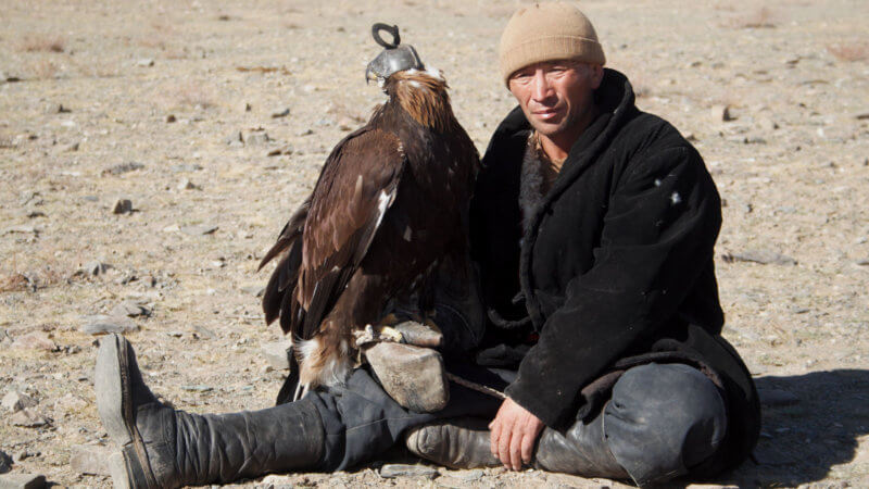 A Kazakh man with one leg crossed holds his eagle.