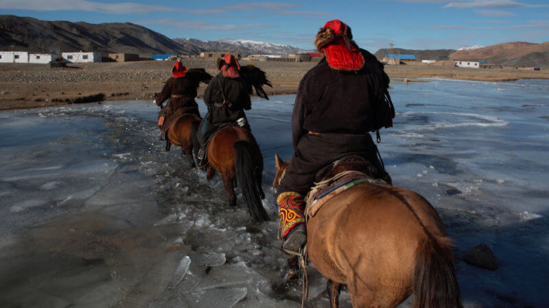 Three eagle hunters riding across a frozen river on horseback holding eagles.