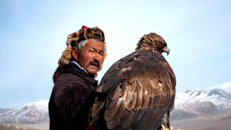 Dalaikhan, a master eagle hunter, holds a hunting eagle on his right arm and looks at the camera.